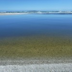 A flat calm river mouth with the ocean swell crashing in on the other side of the spit. Panorama..